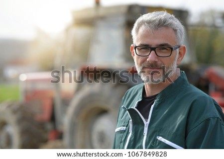 Farmer standing by tractor outside the barn #1067849828