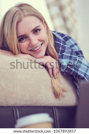 Happy girl online browsing a laptop lying on sofa at home. Freelancing concept. Young smiling girl online browsing a laptop lying on sofa at home. #1067892857