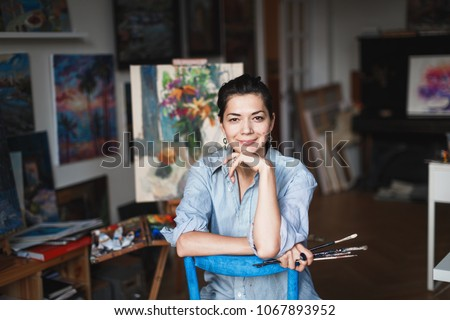 A young smiling brunette woman artist in her Studio is holding a brush. Near her easel, paintings and various art equipment. Royalty-Free Stock Photo #1067893952