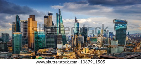London, England - Panoramic skyline view of Bank and Canary Wharf, London's leading financial districts with famous skyscrapers and other landmarks at golden hour sunset with blue sky and clouds #1067911505