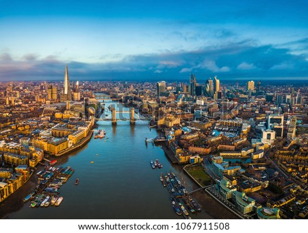 London, England - Panoramic aerial skyline view of London including Tower Bridge with red double-decker bus, Tower of London, skyscrapers of Bank District and Shard skyscraper at golden hour #1067911508