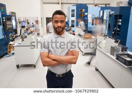 Portrait Of Male Engineer On Factory Floor Of Busy Workshop #1067929802