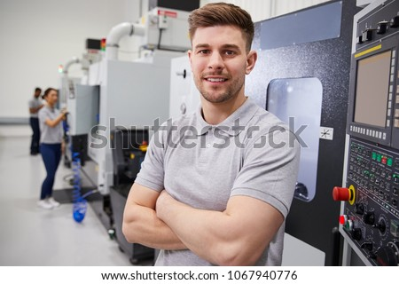 Portrait Of Male Engineer Operating CNC Machinery In Factory #1067940776