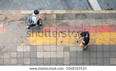 Aerial view and top view with blur man with smartphone is walking in business area with pedestrian street and red and yellow block walkway #1068183533