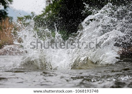 Close-up of water huge splashing in pond from people falling into water, abstract art picture for background