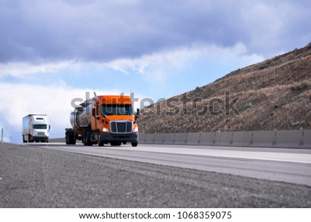 Convoy of the different make and models big rigs semi trucks with tank and dry van semi trailers driving on the road between hills in Oregon to delivery long haul commercial cargo to business partners #1068359075