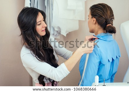 beautiful woman seamstress with long hair and customer. tailor creates an image for the customer in the sewing workshop. dressmaker measures a girl with a measuring tape . Concept Fashion Design #1068380666