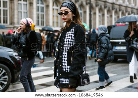PARIS, FRANCE - MARCH 2, 2018:  Aimee Song wears a black and white tweed jacket, black thigh high leather boots, sunglasses, outside BALMAIN show at Paris Fashion Week FW'18-19 #1068419546