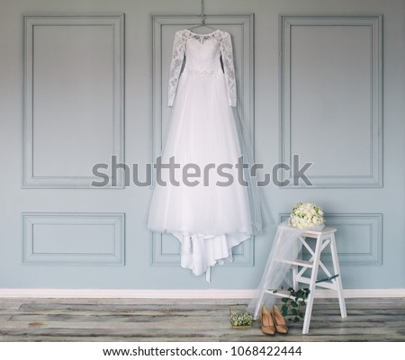 composition - wedding dress on a gray blue wall with decor and accessories Royalty-Free Stock Photo #1068422444