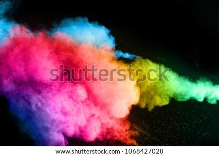 Explosion of color powder on black background. Splash of color powder dust on dark background. #1068427028