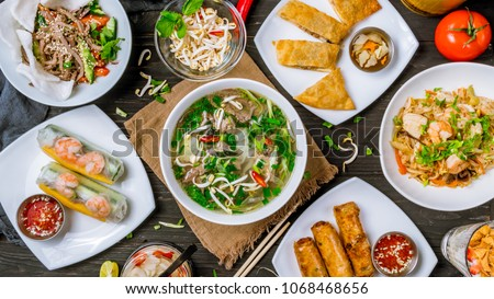 Assorted asian dinner, vietnamese food. Pho ga, pho bo, noodles, spring rolls Royalty-Free Stock Photo #1068468656