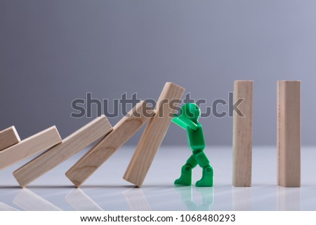 Side View Of A Green Human Figure Stopping Wooden Dominos Blocks Against Grey Background #1068480293