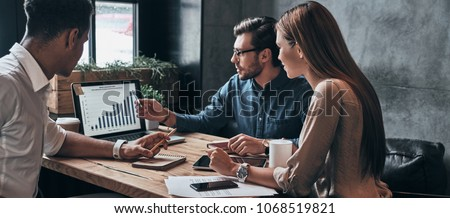 Business professionals. Group of young confident business people analyzing data using computer while spending time in the office #1068519821