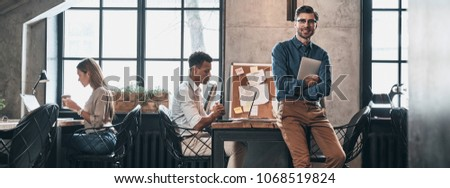 Creative business. Handsome young man in smart casual wear smiling while spending time in the office with his coworkers #1068519824