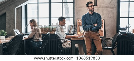 Successful business team. Young modern people in smart casual wear concentrating at work while spending time in the office #1068519833