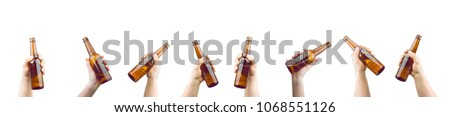 Bunch Of Hands Holding Bottles Of Beer Up At Party Giving A Cheers Isolated On White Background #1068551126