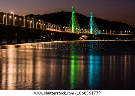 Anita Garibaldi bridge at dusk and illuminated, structure with 2815 meters, is sutuada in the city of Laguna state d Santa Catarina Brazil, Royalty-Free Stock Photo #1068561779