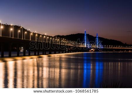 Anita Garibaldi bridge at dusk and illuminated, structure with 2815 meters, is sutuada in the city of Laguna state d Santa Catarina Brazil, Royalty-Free Stock Photo #1068561785