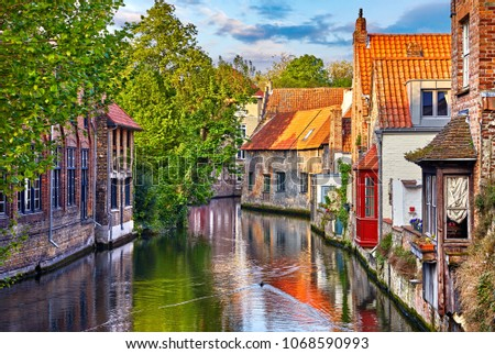 Bruges, Belgium. Medieval ancient houses made of old bricks at water channel with boats in old town. Summer sunset with sunshine and green trees. Picturesque landscape. #1068590993