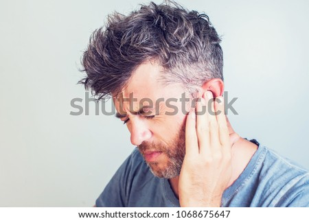 Man with earache is holding his aching ear body pain concept Royalty-Free Stock Photo #1068675647