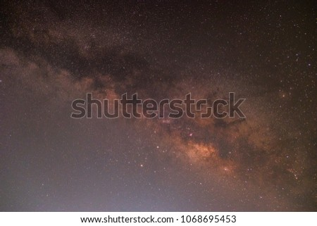 In the night sky the Milky Way and the stars shine in the dark sky. #1068695453