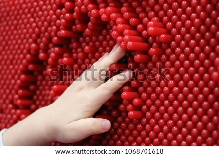 children's hands and pinskreen. child  playing with  contact screen. children's hands  pressed onto the plastic pins on  interactive panel and leave prints. #1068701618