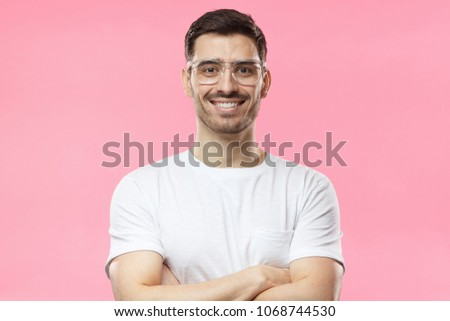 Portrait of smiling handsome man in white t-shirt and transparent eyeglasses standing with crossed arms isolated on pink background #1068744530