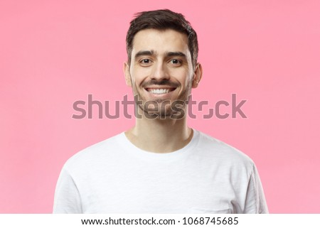 Close up portrait of smiling handsome man in white t-shirt isolated on pink background #1068745685