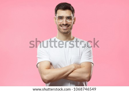 Portrait of smiling handsome man wearing transparent glasses and white tshirt standing with crossed arms isolated on pink background #1068746549