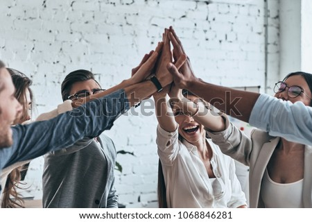 High-five for success! Diverse group of business colleagues giving each other high-five in a symbol of unity and smiling while working in the board room Royalty-Free Stock Photo #1068846281