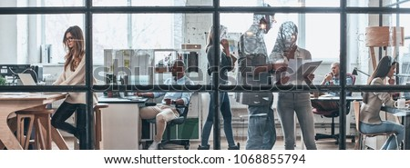 Talking business details. Full length of young modern people working and communicating together while standing behind the glass wall in the board room #1068855794