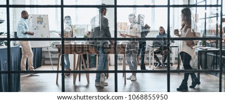 Successful professionals. Large group of young modern people working and communicating together while standing behind the glass wall in the board room #1068855950