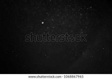 abstract real dust floating over black background for overlay Royalty-Free Stock Photo #1068867965