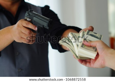 Robbery with gun's. Gun and money in a hands. Bank robbery, Man carrying a gun to rob the bank note. To threaten with the man. A murderer attacking holding gun kidnapping business young person. #1068872558