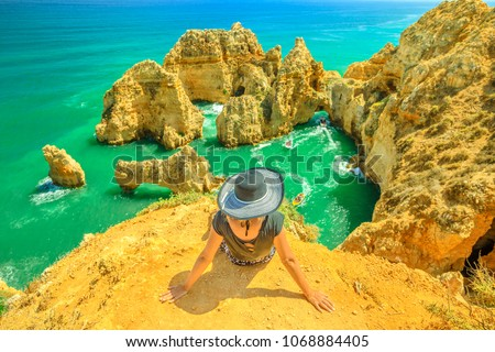 Tourism in Algarve. Summer holidays in Portugal, Europe. Lifestyle tourist sitting on promontory of Ponta da Piedade. Caucasian woman looking amazing views of iconic cliffs of turquoise sea of Lagos. #1068884405
