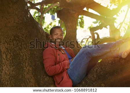 Attractive confident young African-American hipster in formal wear spending time at city garden park.Blurred background #1068891812