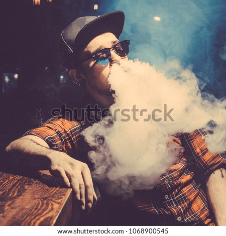 Punk hipster man is smoking a mechanical vape device. Toned image. The concept of popularization of vaping. Vaping man in sunglasses breathes a cloud of steam at the bar square cropping #1068900545