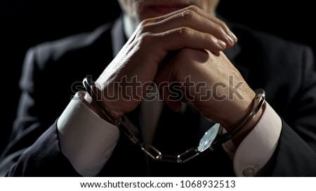 Upset handcuffed man imprisoned for financial crime, punished for serious fraud #1068932513