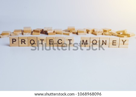 Words PROTECT MONEY made with block wooden letters. Wood abc. on white table #1068968096