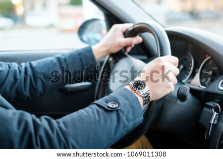 Hand on the wheel of one businessman driving his car #1069011308