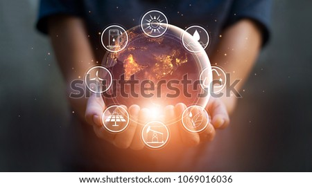 Earth at night was holding in human hands with energy resources icon. Earth day. Energy saving concept #1069016036