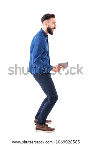Childish playful expressive young adult business man holding cellphone as pistol and aiming away. Full body isolated on white background. #1069028585