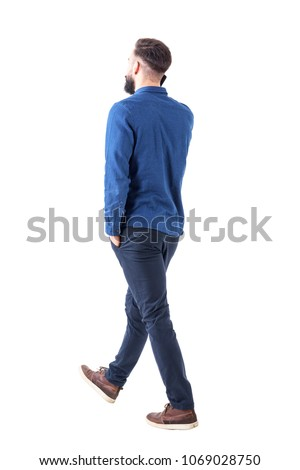 Side back view of young smart casual business man talk on the cellphone walking away. Full body isolated on white background. #1069028750