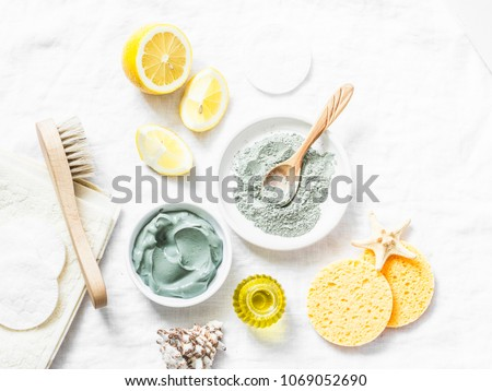 Homemade beauty facial mask. Clay, lemon, oil, facial brush - beauty products ingredients on light background, top view Royalty-Free Stock Photo #1069052690