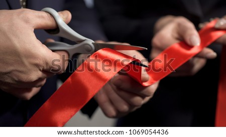 Business people hands cutting red ribbon close-up, new project, opening ceremony, stock footage Royalty-Free Stock Photo #1069054436