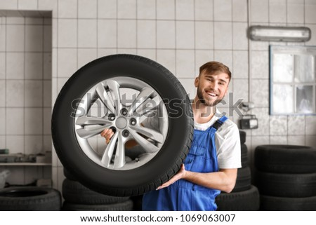 Mechanic with car wheel in repair shop. Tire service #1069063007
