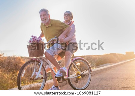 joy and happiness for adult married couple start and have fun traveling on the same bike in outdoor activity with sun backlight on the background. clear and bright image for smile and laugh people.  #1069081127