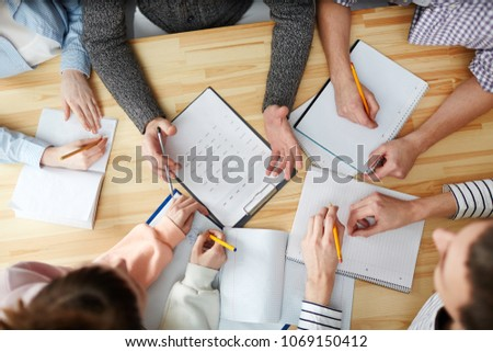 Overview of hands of students making notes and teacher answering their questions by desk Royalty-Free Stock Photo #1069150412