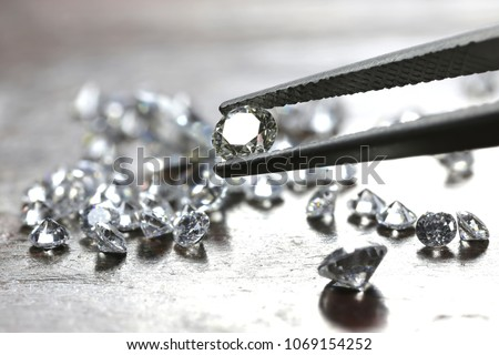 brilliant cut diamond held by tweezers #1069154252