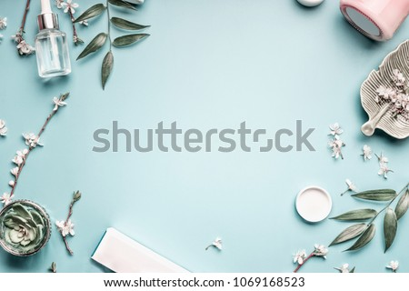 Beauty background with facial cosmetic products, leaves and cherry blossom on pastel blue desktop background. Modern spring skin care layout, top view, flat lay.  #1069168523